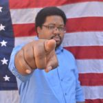 Original Freedom Writer Narada pointing in front of an American Flag